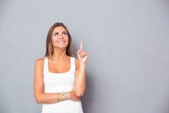 Jovem mulher de sorriso que aponta o dedo acima Fotografia de Stock