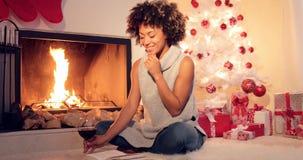 Jovem mulher de sorriso que aprecia um livro no Natal imagens de stock royalty free
