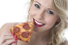 Jovem mulher de sorriso que come a fatia da pizza Imagens de Stock Royalty Free