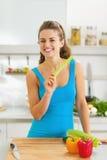 Jovem mulher de sorriso que come o aipo na cozinha moderna Fotografia de Stock Royalty Free