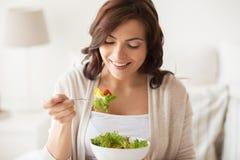 Jovem mulher de sorriso que come a salada em casa Fotografia de Stock