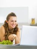 Jovem mulher de sorriso que come a uva e a utilização do portátil na cozinha Foto de Stock