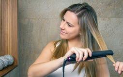 Jovem mulher de sorriso que endireita o cabelo com a imagens de stock royalty free