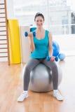 Jovem mulher de sorriso que exercita com pesos na bola da aptidão Foto de Stock Royalty Free