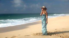 Jovem mulher de sorriso que fala no telefone celular na praia vídeos de arquivo