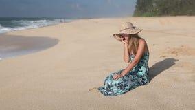 Jovem mulher de sorriso que fala no telefone celular na praia filme