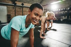Jovem mulher de sorriso que faz flexões de braço durante uma sessão do exercício do gym foto de stock