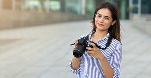 Jovem mulher de sorriso que guarda a câmera fora com espaço da cópia Fotógrafo, turista foto de stock royalty free