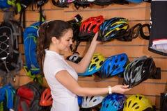 jovem mulher de sorriso que guarda capacetes da bicicleta fotos de stock