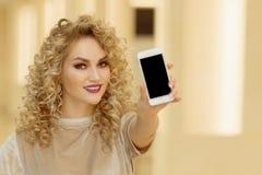 Jovem mulher de sorriso que guarda o telefone celular na alameda fotografia de stock