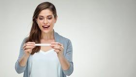 Jovem mulher de sorriso que guarda o teste grávido branco Fotos de Stock Royalty Free