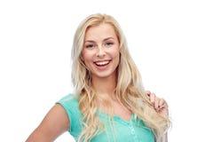 Jovem mulher de sorriso que guarda sua costa do cabelo Fotos de Stock Royalty Free