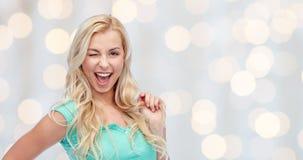 Jovem mulher de sorriso que guarda sua costa do cabelo Foto de Stock