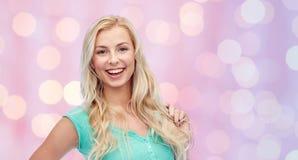 Jovem mulher de sorriso que guarda sua costa do cabelo Imagens de Stock Royalty Free