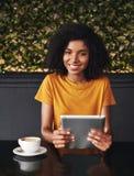 Jovem mulher de sorriso que guarda a tabuleta digital à disposição foto de stock