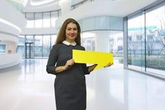 Jovem mulher de sorriso que guarda uma placa amarela nas mãos Foto de Stock