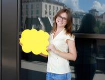 Jovem mulher de sorriso que guarda uma placa amarela nas mãos Imagens de Stock Royalty Free