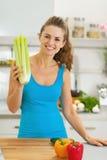 Jovem mulher de sorriso que guardara o aipo na cozinha moderna Foto de Stock