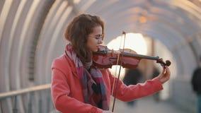 Jovem mulher de sorriso que joga o violino na passagem aérea Ajustando o violino video estoque