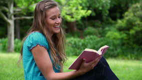 Jovem mulher de sorriso que lê uma novela video estoque