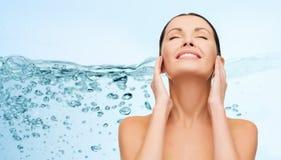Jovem mulher de sorriso que limpa sua cara sobre a água Foto de Stock Royalty Free