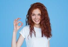 Jovem mulher de sorriso que mostra o sinal APROVADO Foto de Stock
