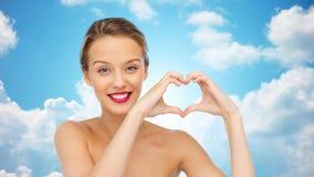 Jovem mulher de sorriso que mostra o sinal da mão da forma do coração Fotografia de Stock Royalty Free