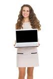 Jovem mulher de sorriso que mostra a portátil a tela vazia Imagem de Stock Royalty Free