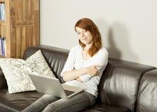 Jovem mulher de sorriso que relaxa com seu portátil Fotos de Stock