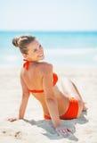 Jovem mulher de sorriso que senta-se na praia Fotos de Stock