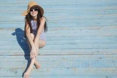 Jovem mulher de sorriso que senta-se na praia Fotos de Stock Royalty Free