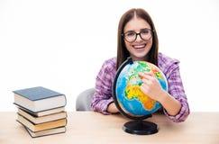 Jovem mulher de sorriso que senta-se na tabela com globo Imagem de Stock