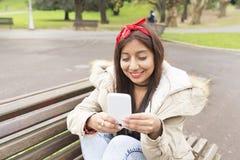 Jovem mulher de sorriso que senta-se no banco de madeira e em usar o telefone esperto Imagens de Stock