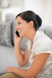Mulher de sorriso que senta-se no sofá e no telefone de fala Fotos de Stock Royalty Free