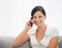 Mulher de sorriso que senta-se no sofá e no móbil de fala imagens de stock