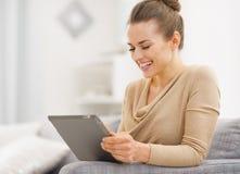 Jovem mulher de sorriso que senta-se no sofá e que trabalha no PC da tabuleta fotos de stock royalty free