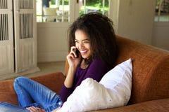 Jovem mulher de sorriso que senta-se no sofá que fala no telefone celular Foto de Stock Royalty Free