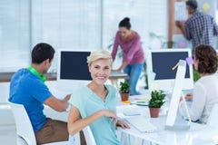 Jovem mulher de sorriso que trabalha com seu colega na mesa Imagens de Stock
