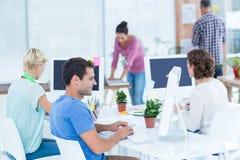 Jovem mulher de sorriso que trabalha com seu colega na mesa Imagem de Stock