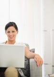 Jovem mulher de sorriso que usa o portátil foto de stock royalty free