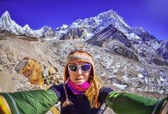 A jovem mulher de sorriso toma um selfie no pico de montanha Fotos de Stock Royalty Free