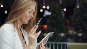 A jovem mulher de sorriso toma uns dados do cartão de crédito dourado que trabalha com uma tabuleta video estoque