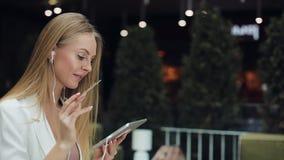 A jovem mulher de sorriso toma uns dados do cartão de crédito dourado que trabalha com uma tabuleta filme