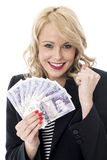 Jovem mulher deleitada que guarda a moeda do dinheiro Foto de Stock