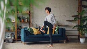 A jovem mulher delgada é concentrada em exercícios de equilíbrio durante pessoal treinando em casa estar no assoalho em um pé filme