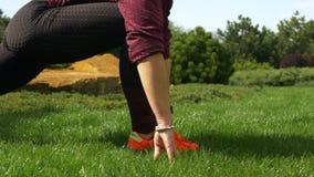 Jovem mulher delgada e bonita no sportswear que prepara-se para exercícios no gramado perto de sua casa, fazendo exercícios para  filme