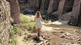 A jovem mulher delgada no vestido de cocktail cinzento curto anda abaixo do rio pequeno com o telefone em sua mão, senhora com o  filme