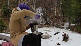 A jovem mulher derrama o chá de uma garrafa térmica perto de um córrego na floresta do inverno vídeos de arquivo