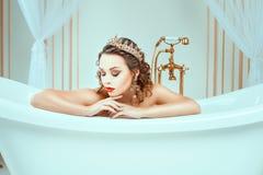 Jovem mulher despida bonita que senta-se no banho caro da joia imagens de stock