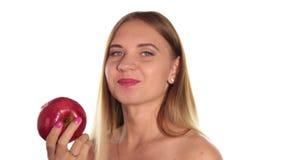 A jovem mulher despida veste o batom vermelho e tem seu cabelo para baixo, e escovado, comendo um grande, obscuridade - maçã verm filme